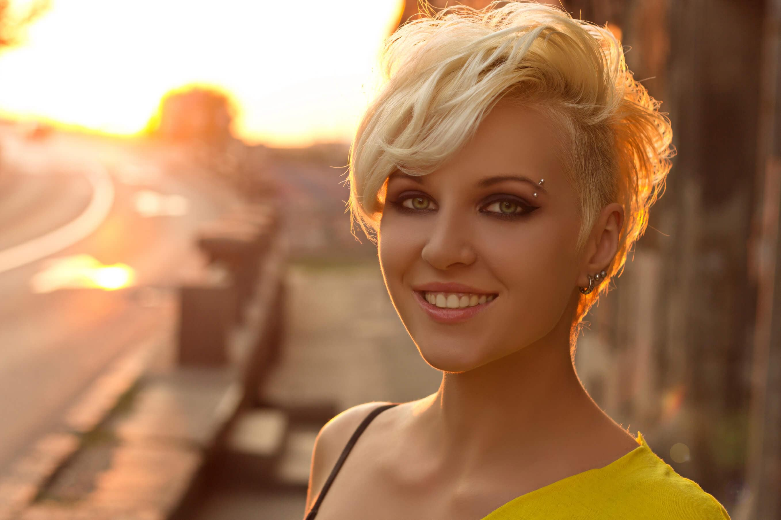 a blonde woman with short pixie hair cut standing outside