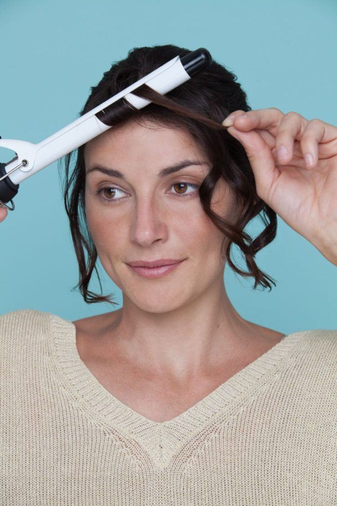 woman with short hair curling hair with a curling iron