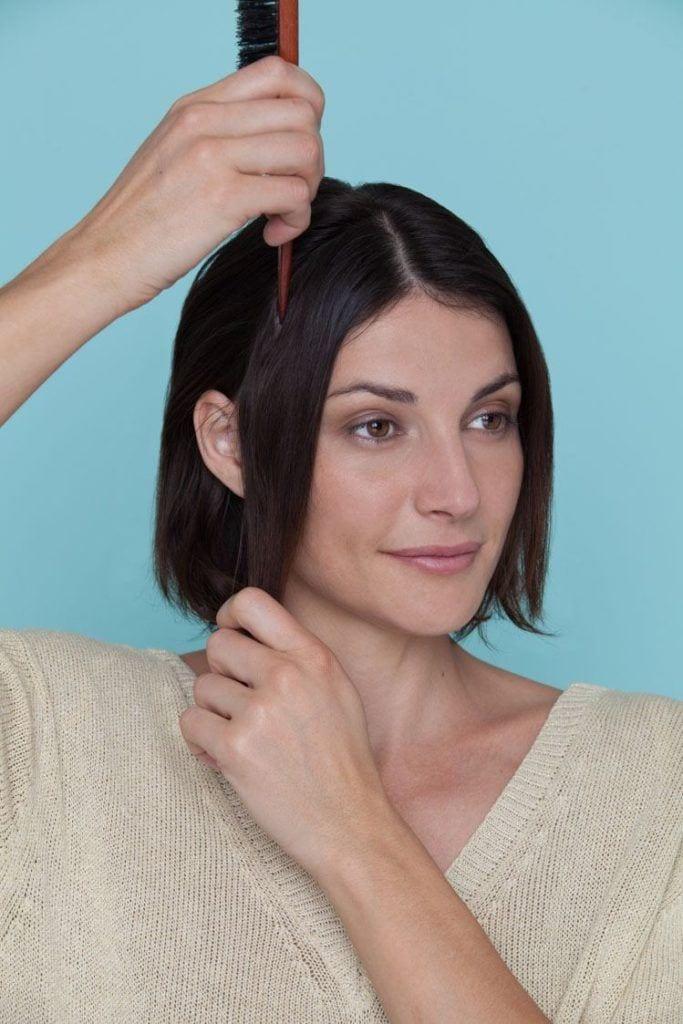 woman with bob haircut parting hair