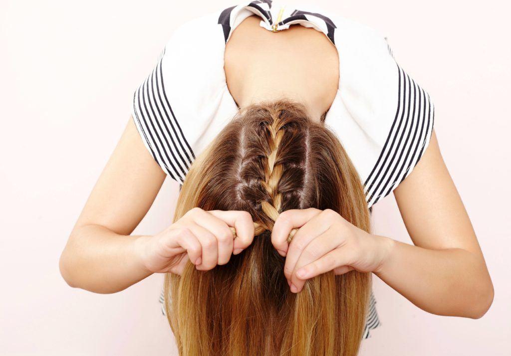 woman creating upside down braid on her hair