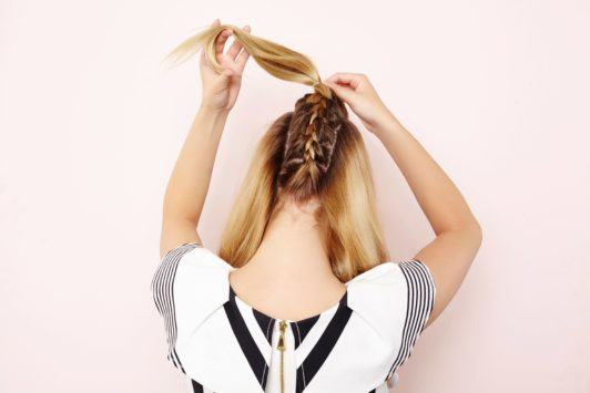 woman creating ponytail on braided hairstyle