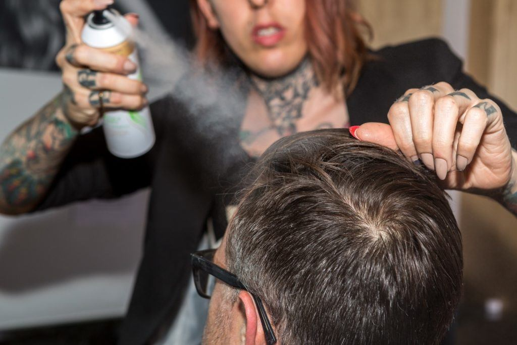 hairstylist applying hairspray to clients hair