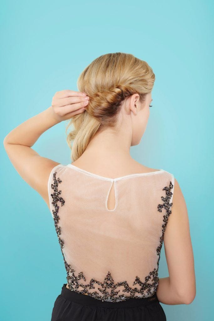 blonde woman creating croissant bun on hair