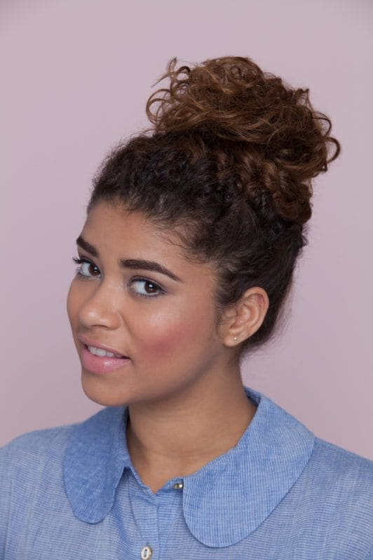 young woman wearing curly braided updo knot hairstyle