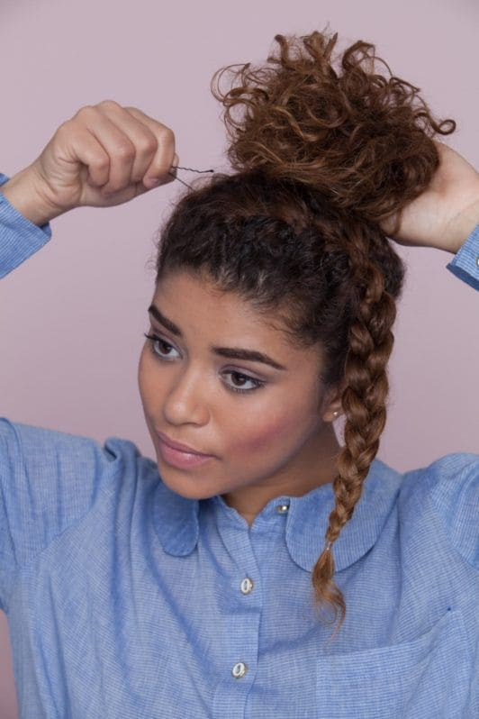 young woman with curly hair creating bun