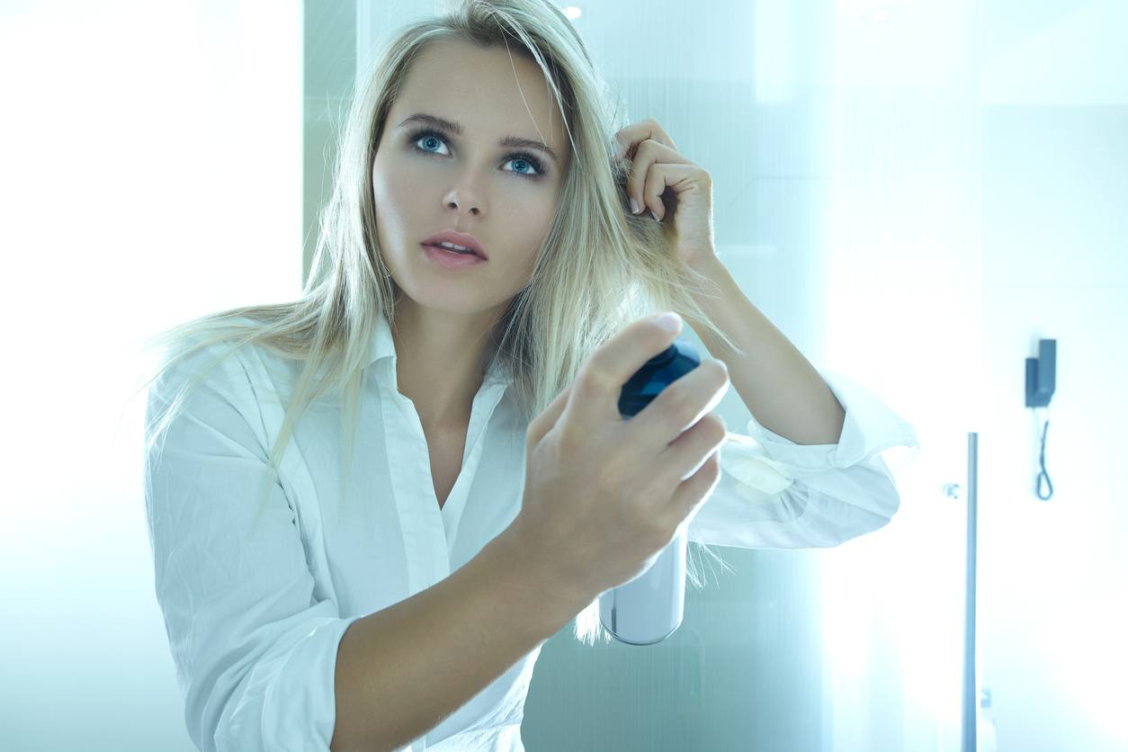 young blonde woman doing herself applying dry shampoo to hair. View from the mirror. dry shampoo cause hair loss myth