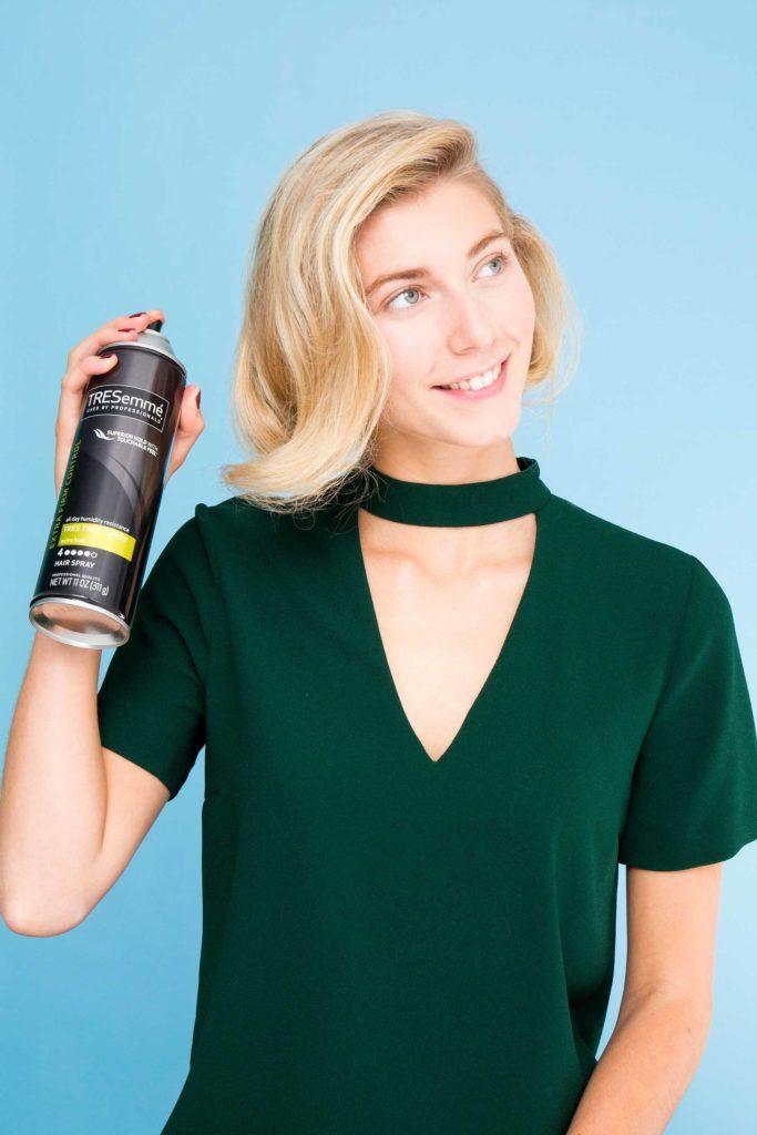 blonde woman applying hairspray