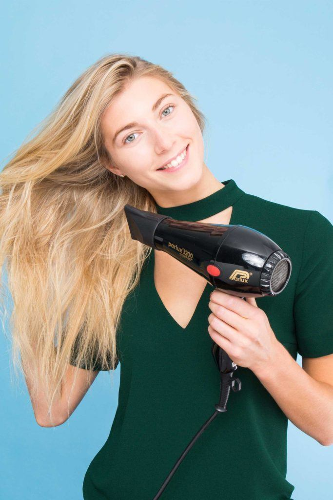 blonde woman blowdrying her hair