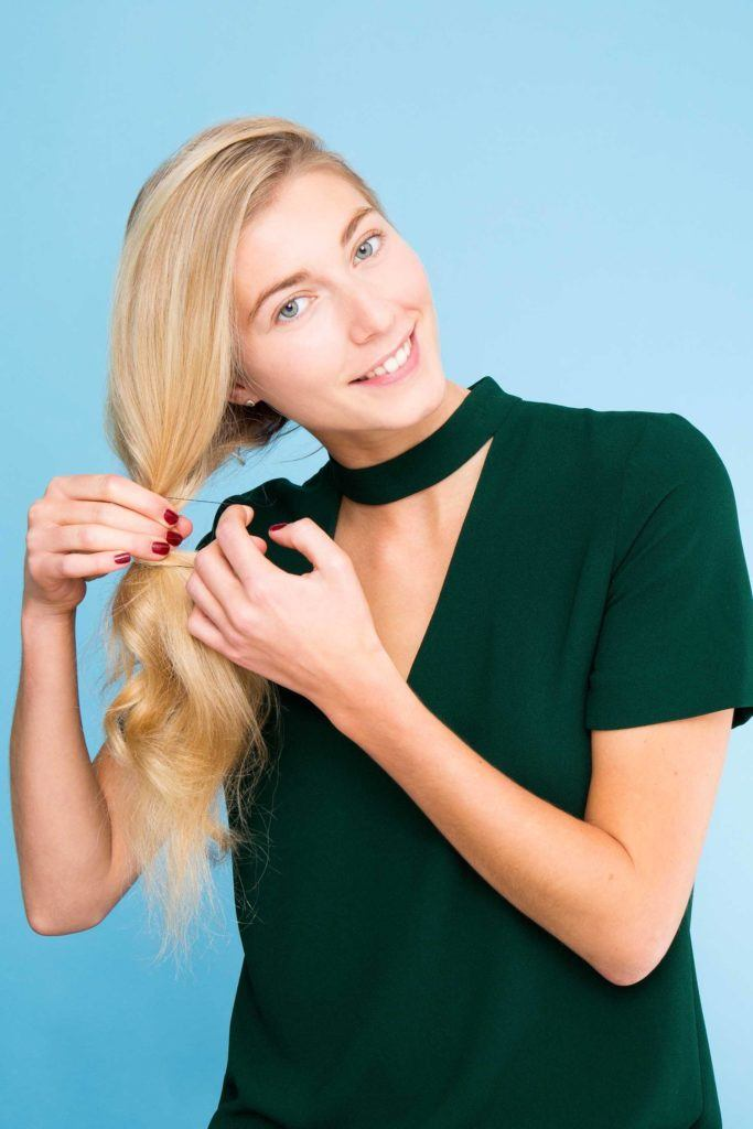 blonde woman styling hair into a ponytail