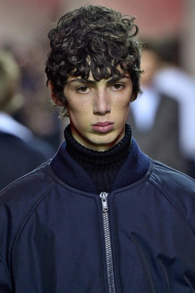 a curly man with bangs wearing blue jacket
