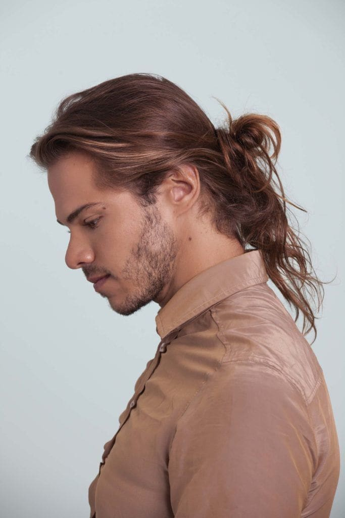 man posing with messy low bun hairstyle