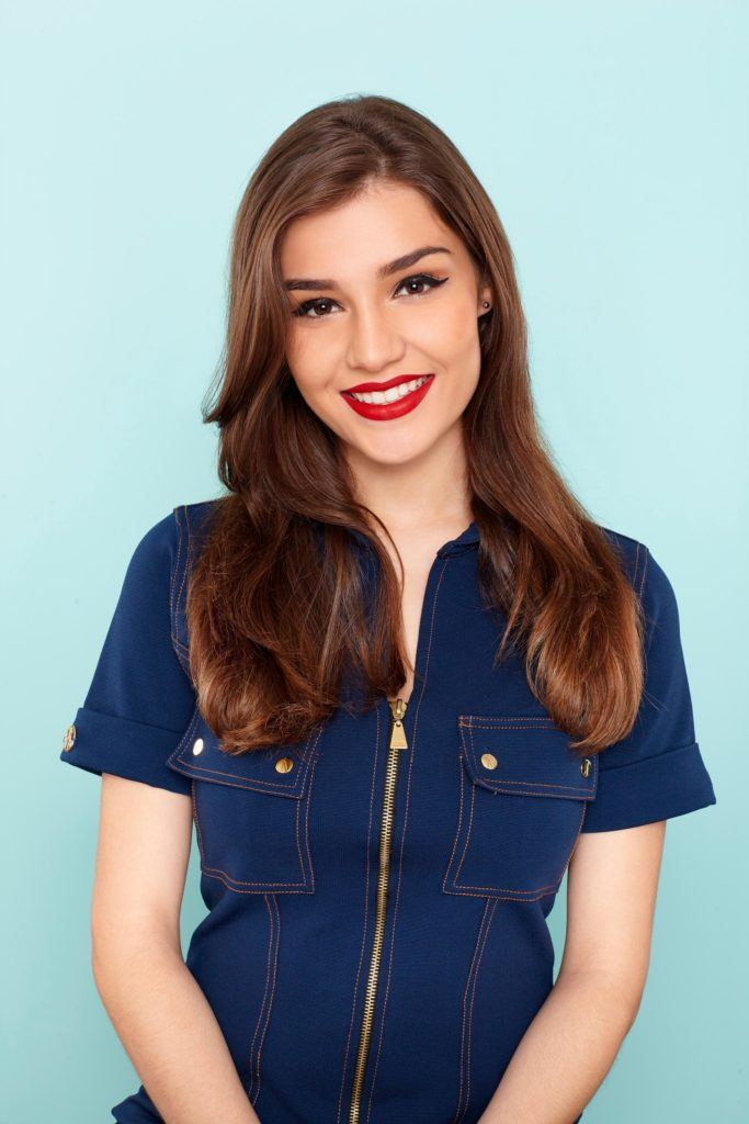 a smiling woman with side-swept waves hair wearing blue shirt