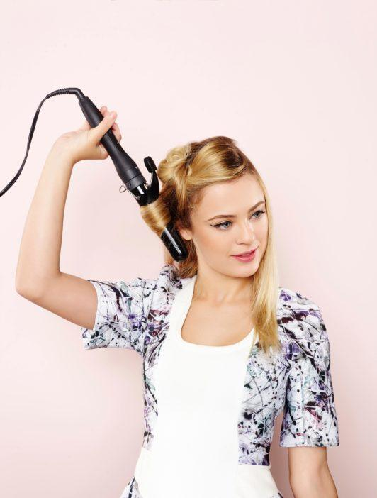 woman with long straight blonde hair curling back of hair