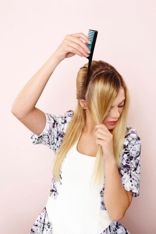 woman with long straight blonde hair parting her hair