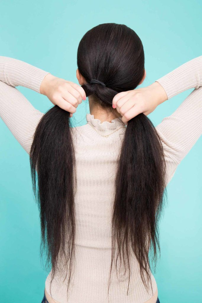 woman tightening ponytail on long hair