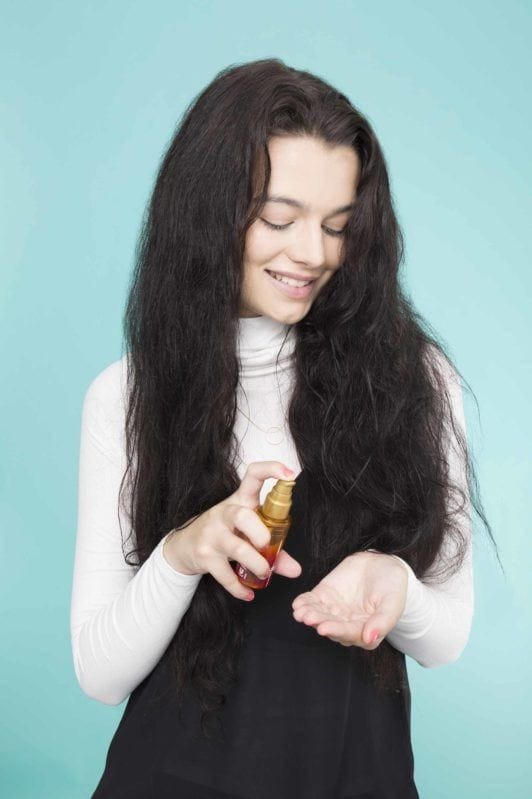 young lady with long black hair applying serum