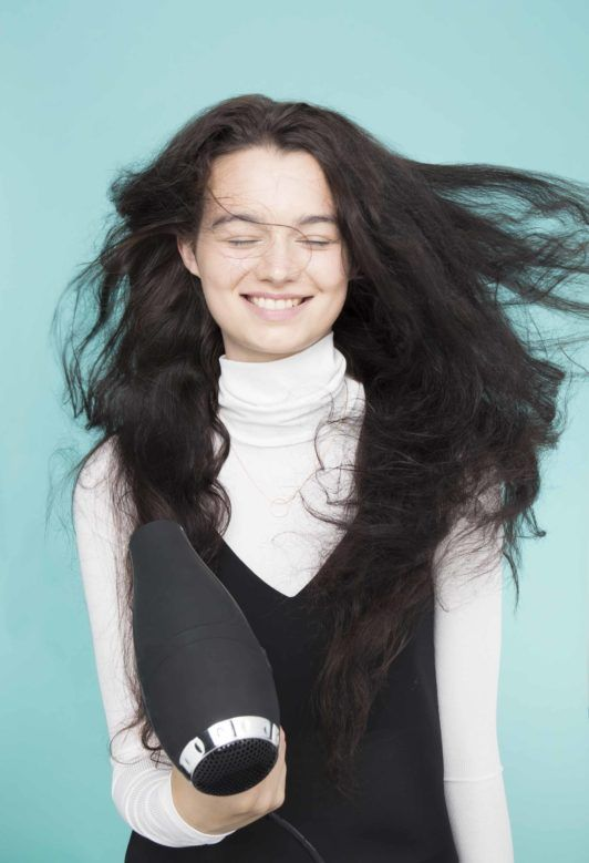 young lady with long black hair blowdrying hair