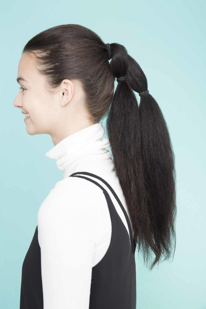 young lady with long black hair showing side view of bubble pony