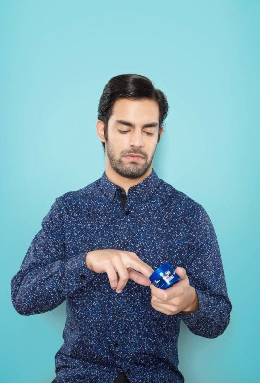 man scooping out hair pomade for hair styling