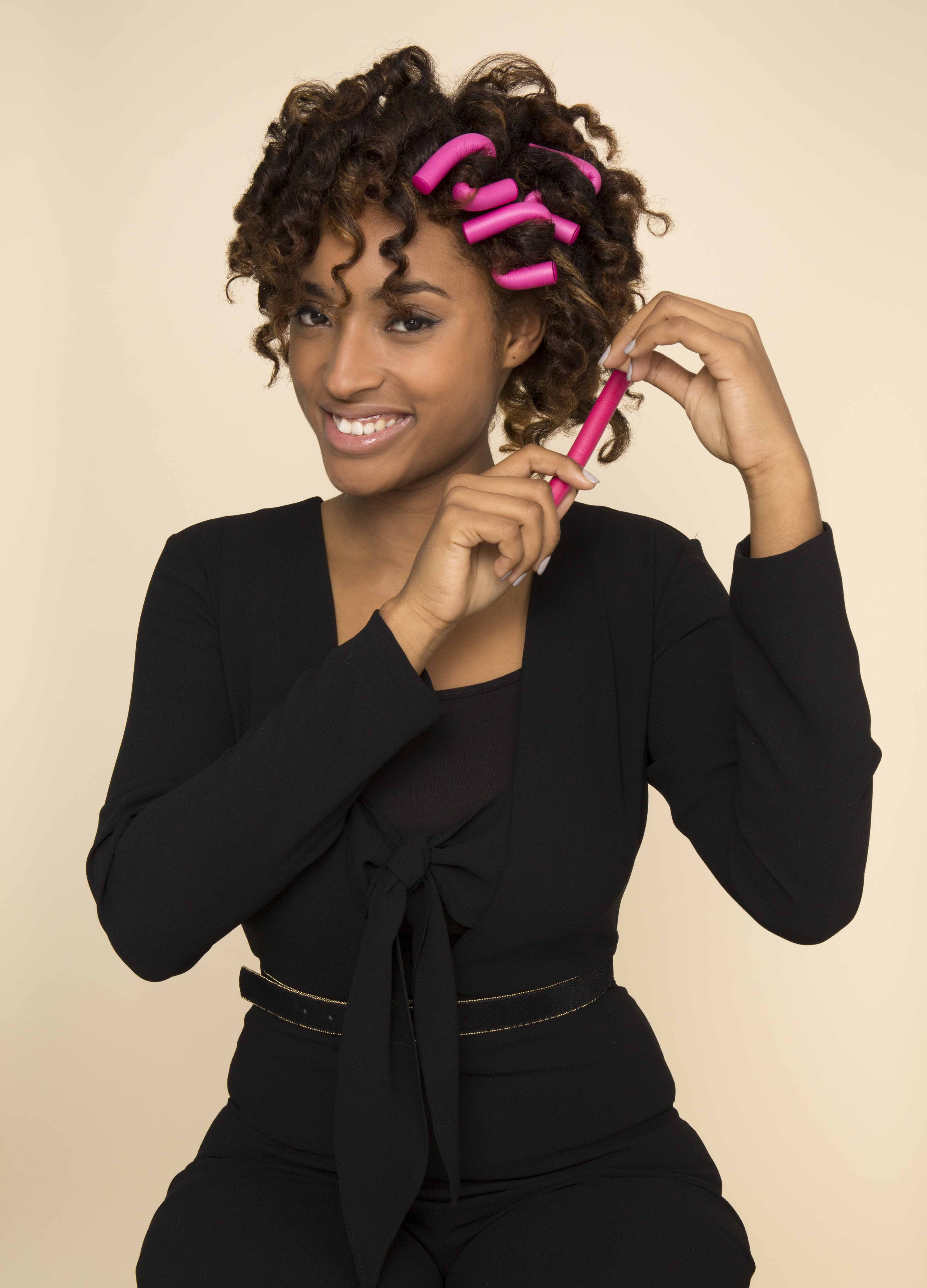 young woman styling curly hair with flexi-rods