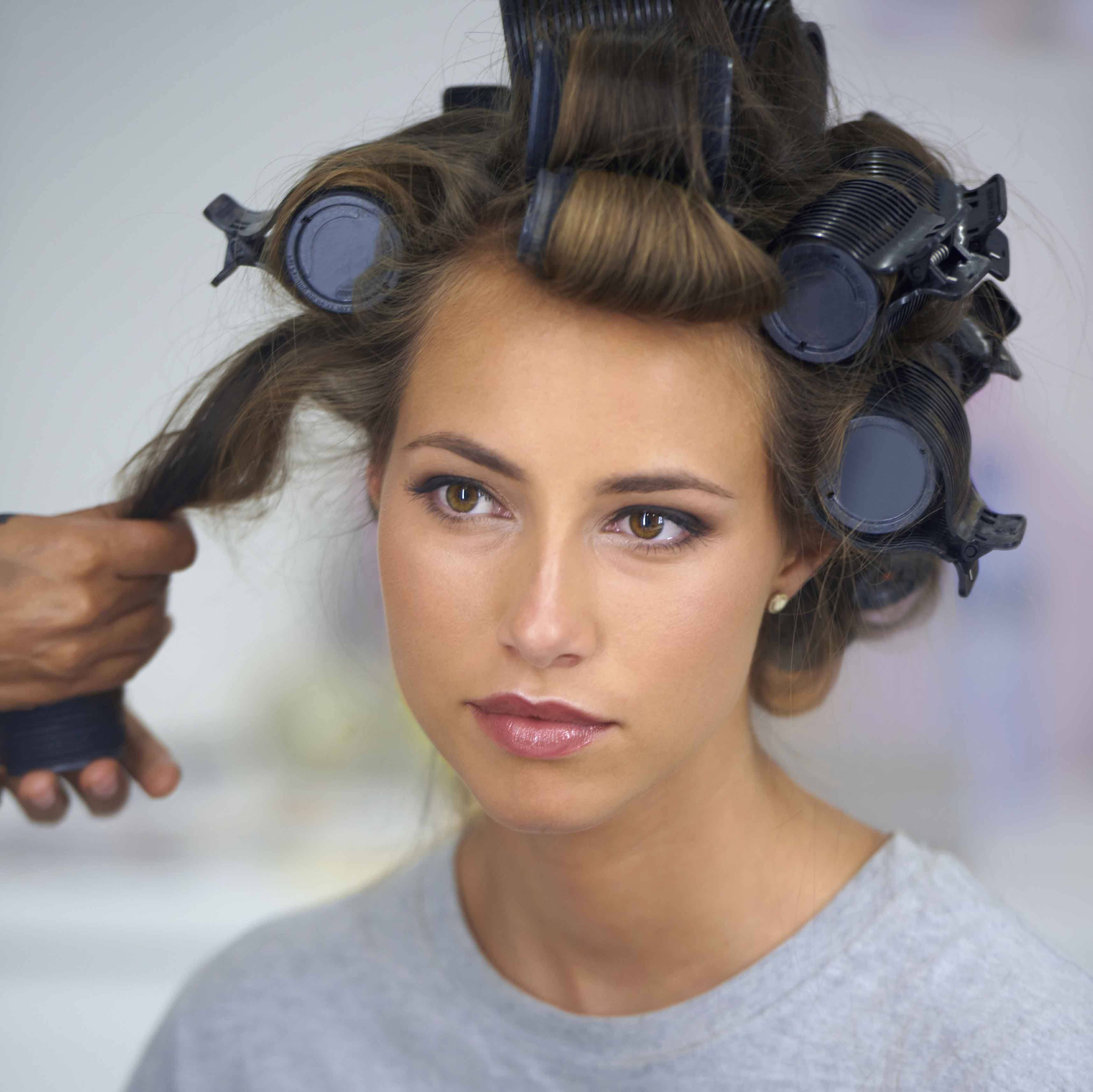 young woman getting hair styled with hot rollers