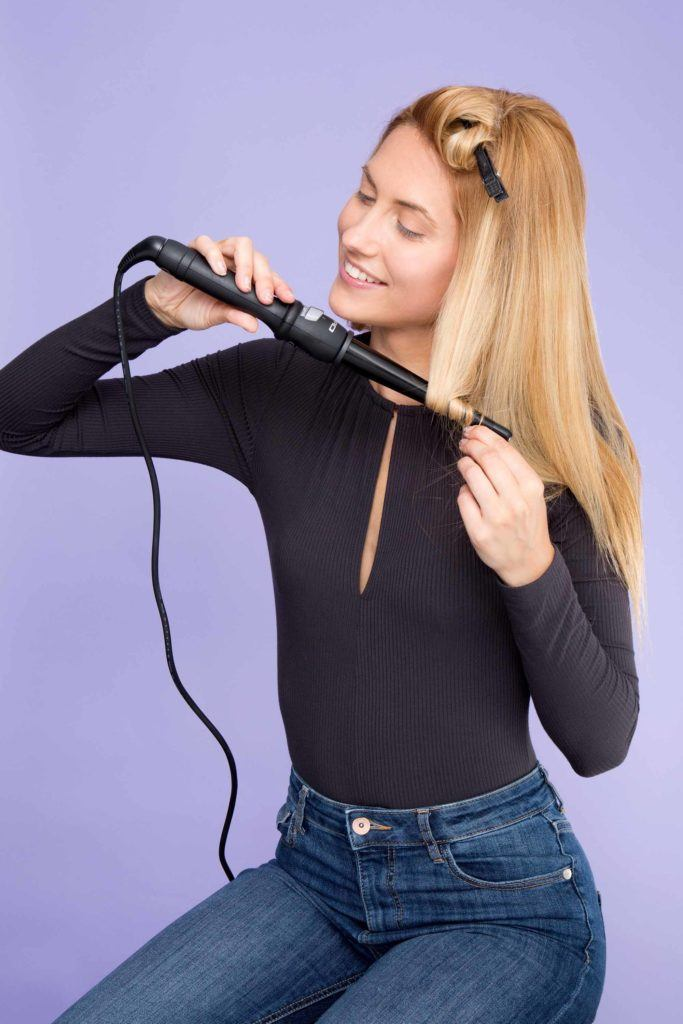 woman with blonde hair curling hair ends with hair wand