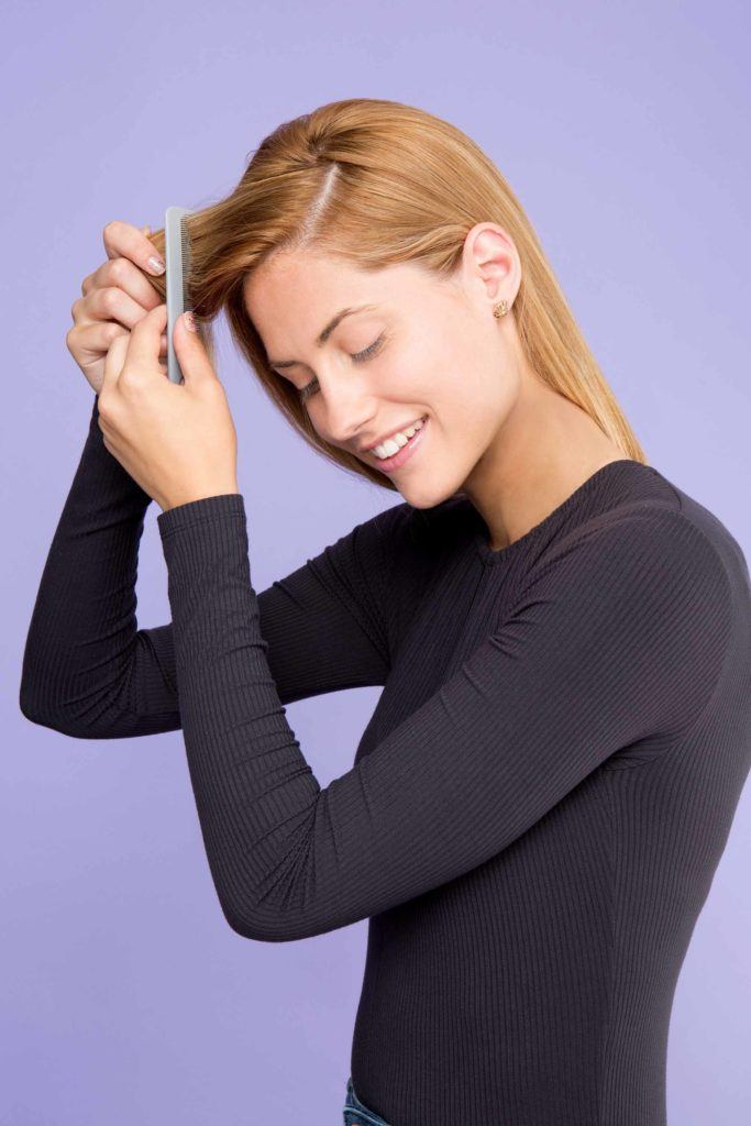 woman with blonde hair combing hair
