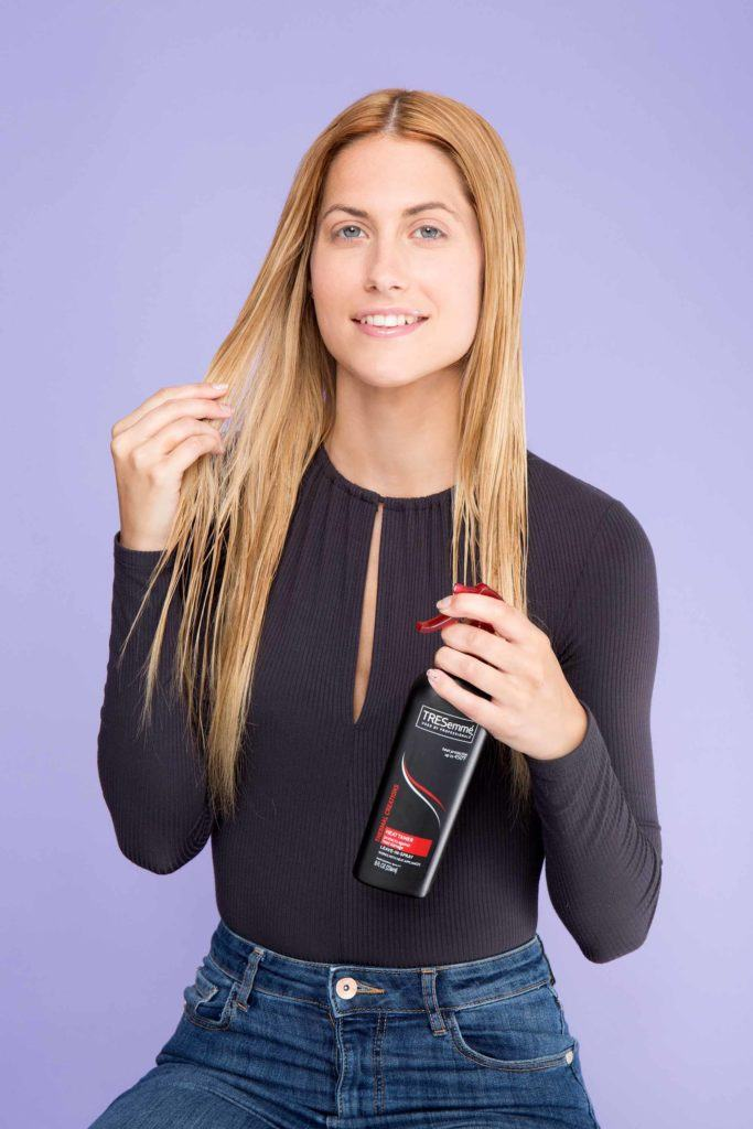 woman with blonde hair applying heat protectant spray to hair
