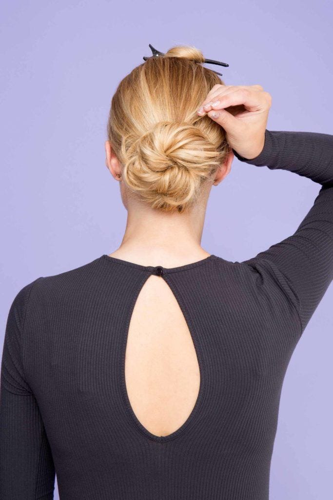 woman with blonde hair creating bun hairstyle