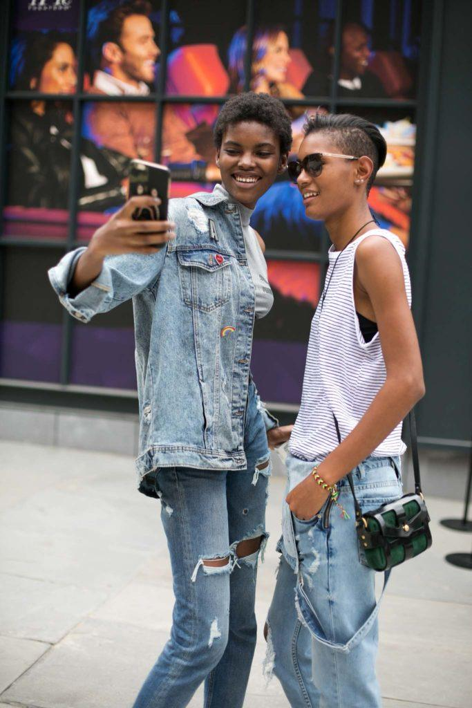 two women taking a selfie in the middle of the pedestrian wearing denim outfits