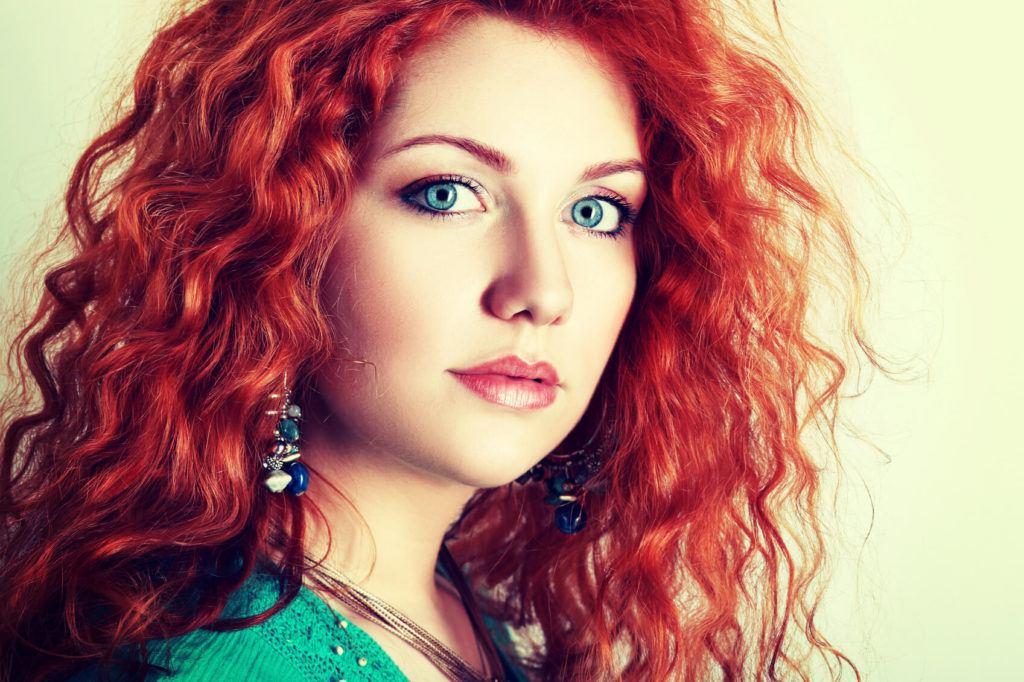 Beautiful women with blood orange hair worn in natural curls