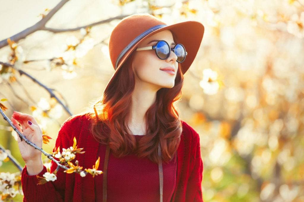 Beautiful women with blood orange hair worn in soft waves