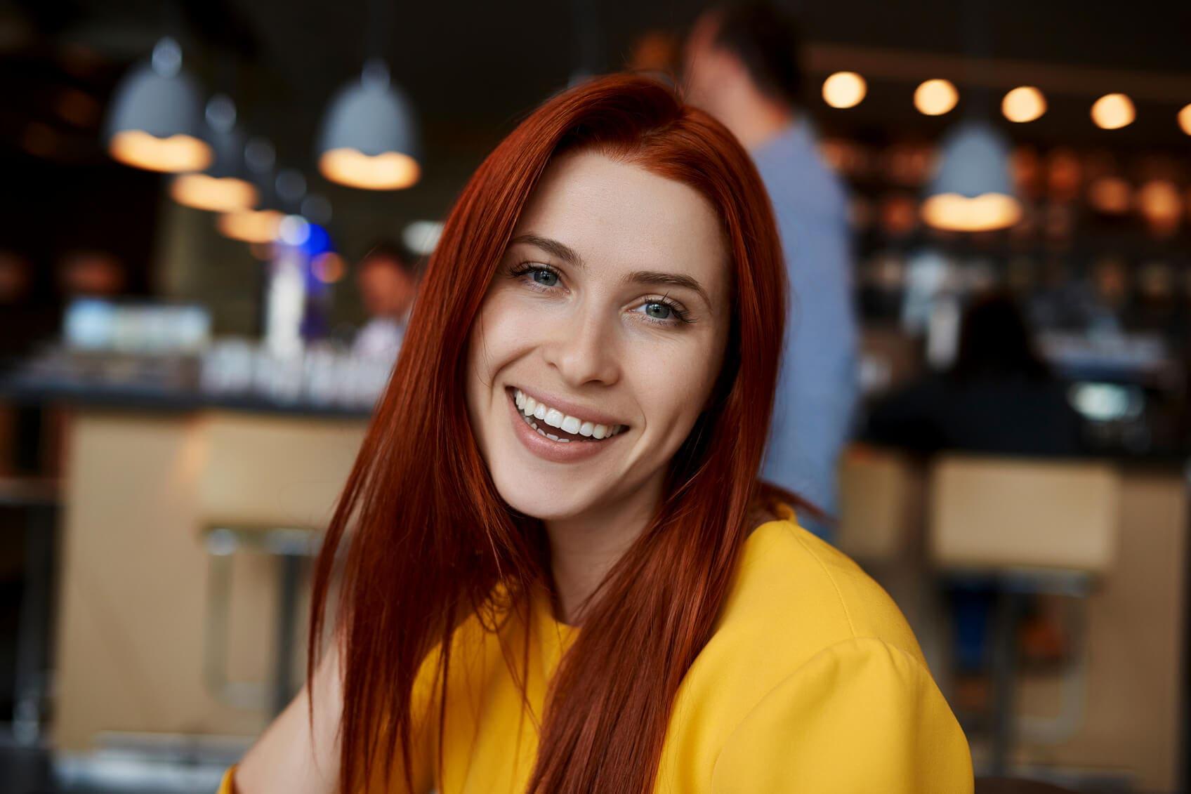 Beautiful women with blood orange hair worn in straight blowout