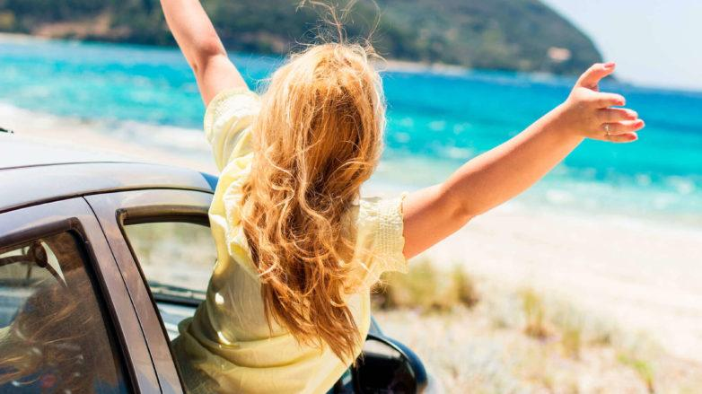 a long blonde woman in a car at the beach