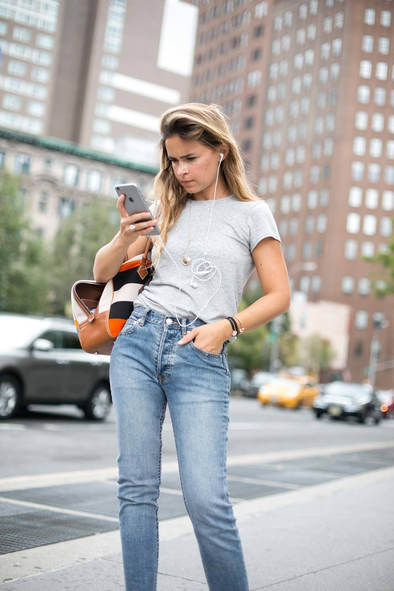 young woman with long hair searching on cell phone for best hair care buys