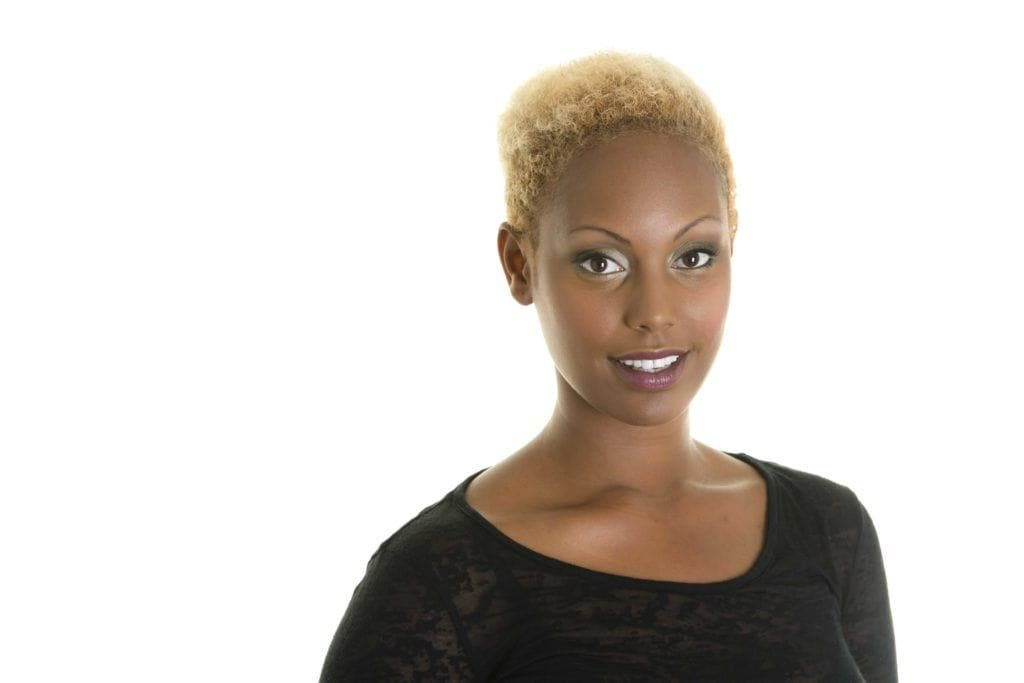 Beautiful woman with a blonde afro short haircut smiling at camera