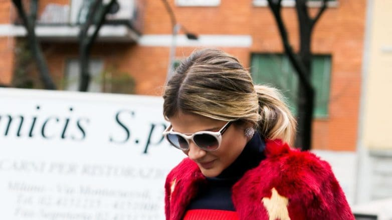 a woman walking on the street wearing red dress and sunglasses with ponytail blond hair