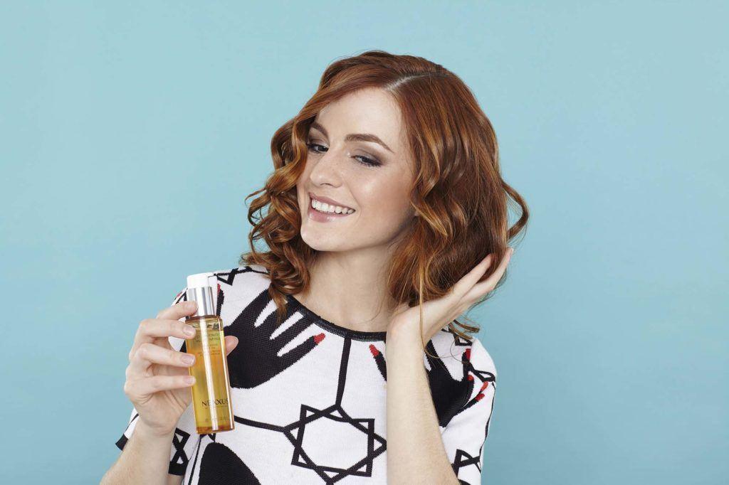 woman adding nexxus oil to her hair
