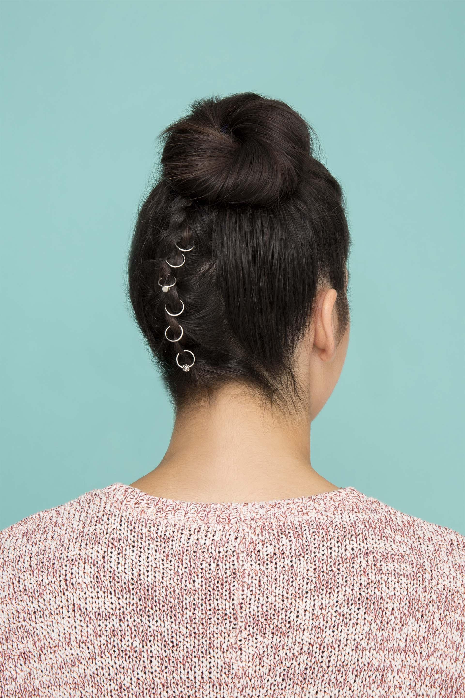 Woman wearing pierced festival braids in an updo.
