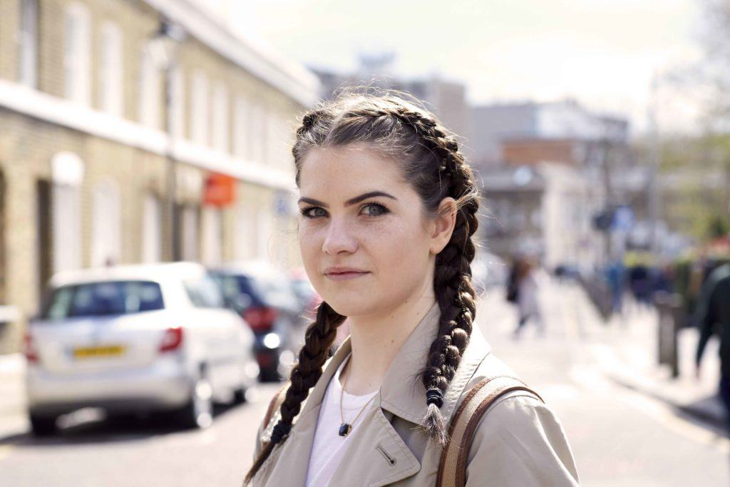 a woman with ponytail braid standing on the street