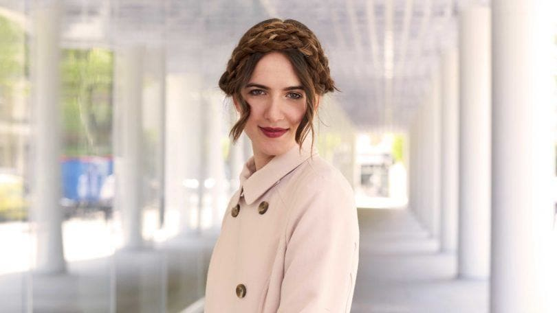 a woman with milkmaid braid standing in a hall