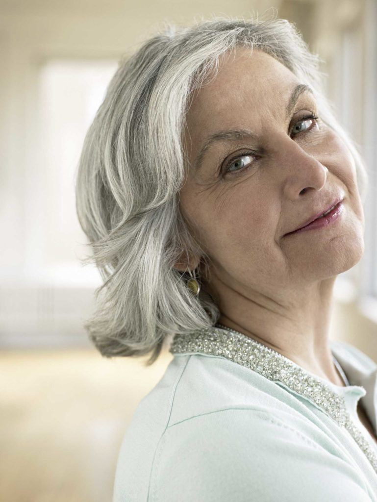 an old lady with short gray hair flipped over smiling forward