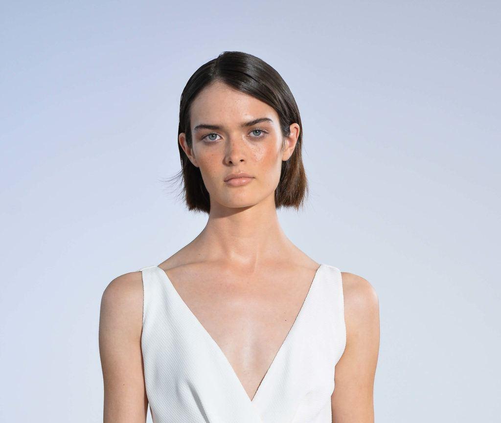 a female model with short sleek haircut wearing a white dress staring forward