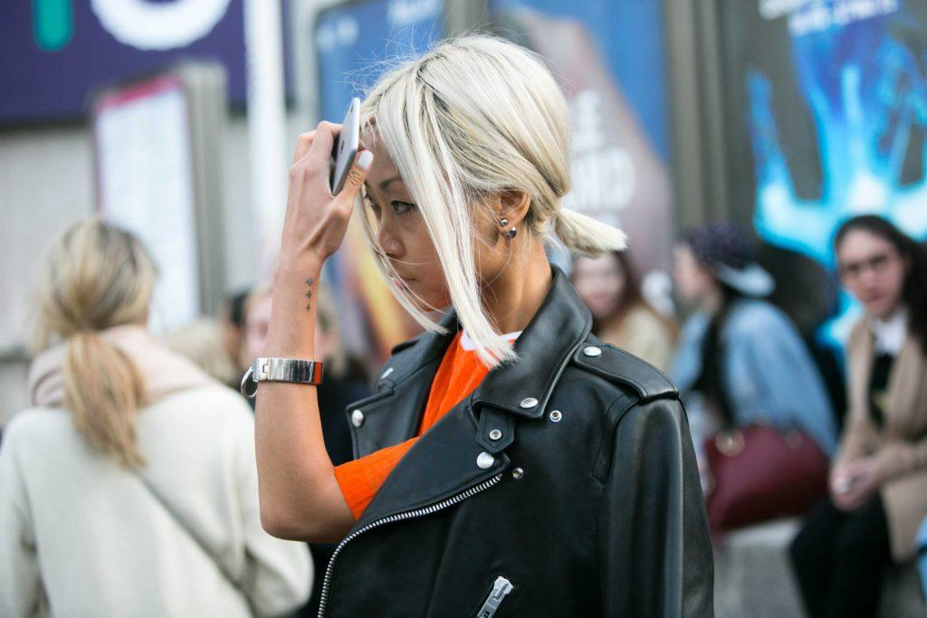 an asian woman with platinum short ponytail wearing leather jacket standing in a crowd
