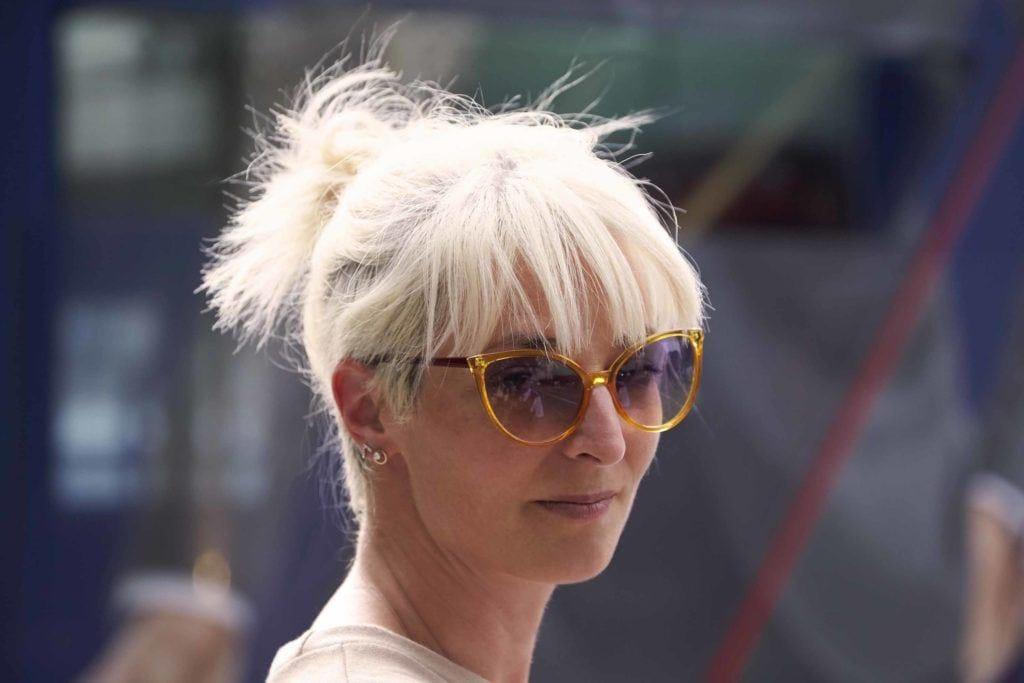 a blonde woman wearing sunglasses with undercut bun