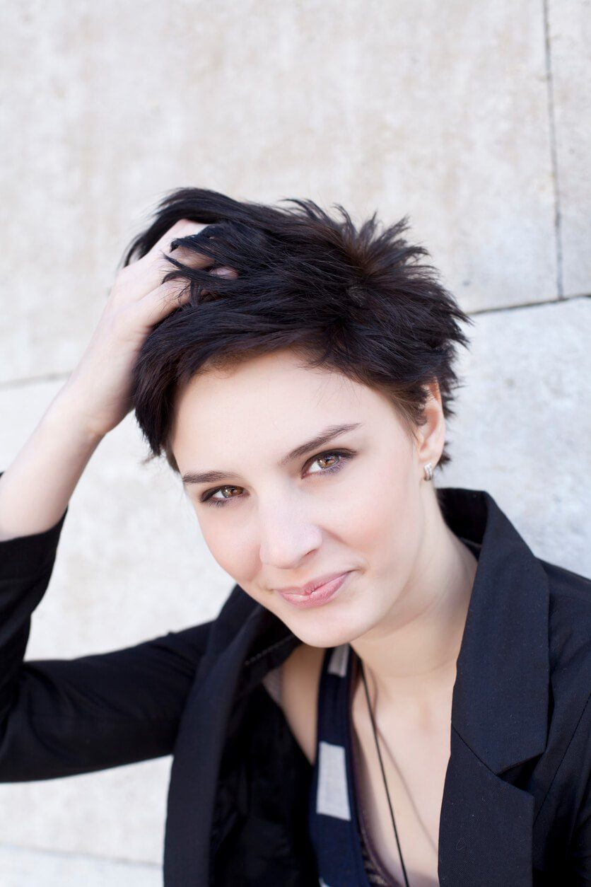 woman with pixie haircut in jet black with spiky ends.