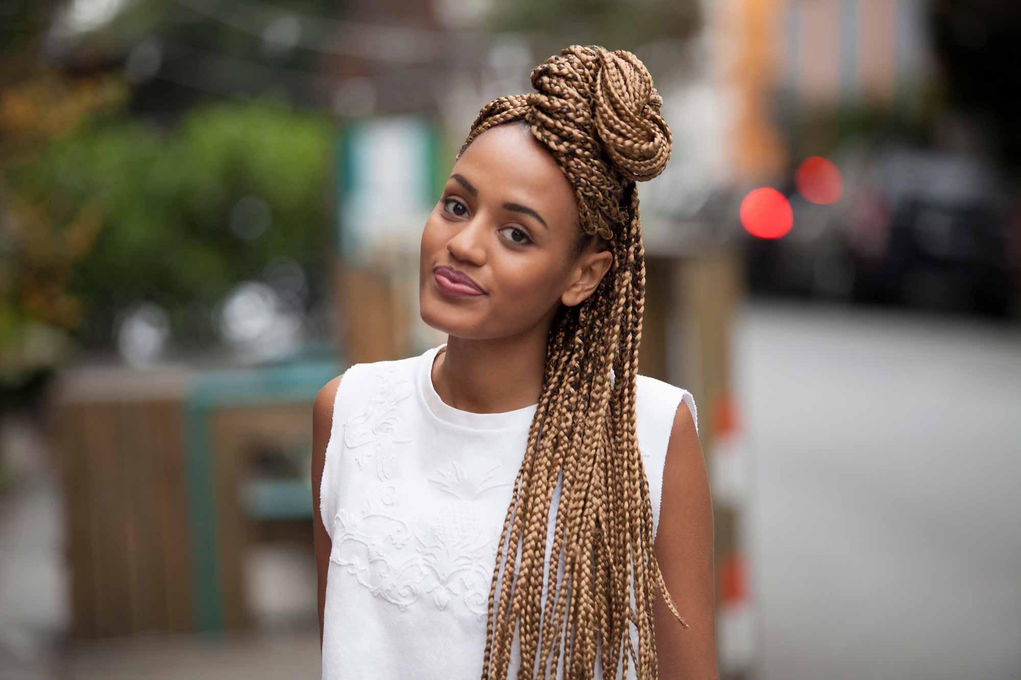 Woman wearing cute spring break hair looks: half up top knot.