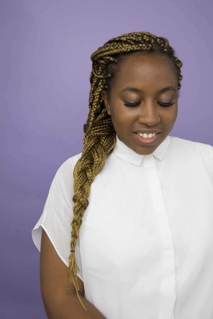 Woman using transitioning hairstyles to grow out chemically straightened hair. box braid extensions.