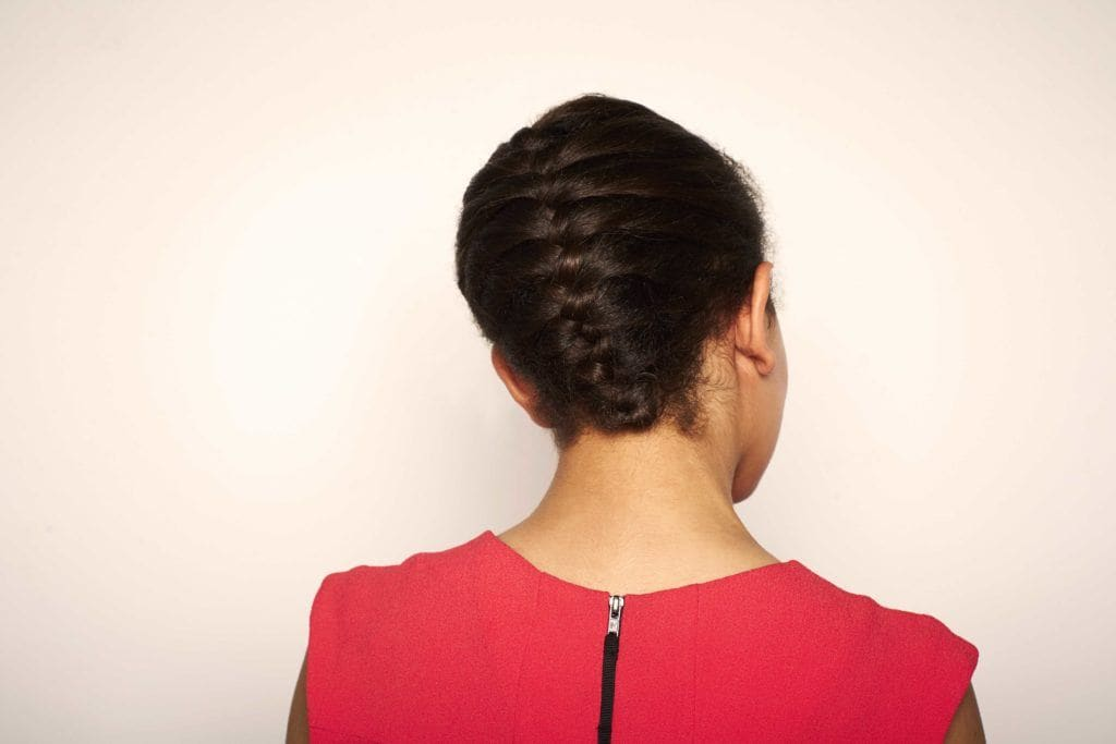 Woman using transitioning hairstyles to grow out chemically straightened hair. Tucked french braid.