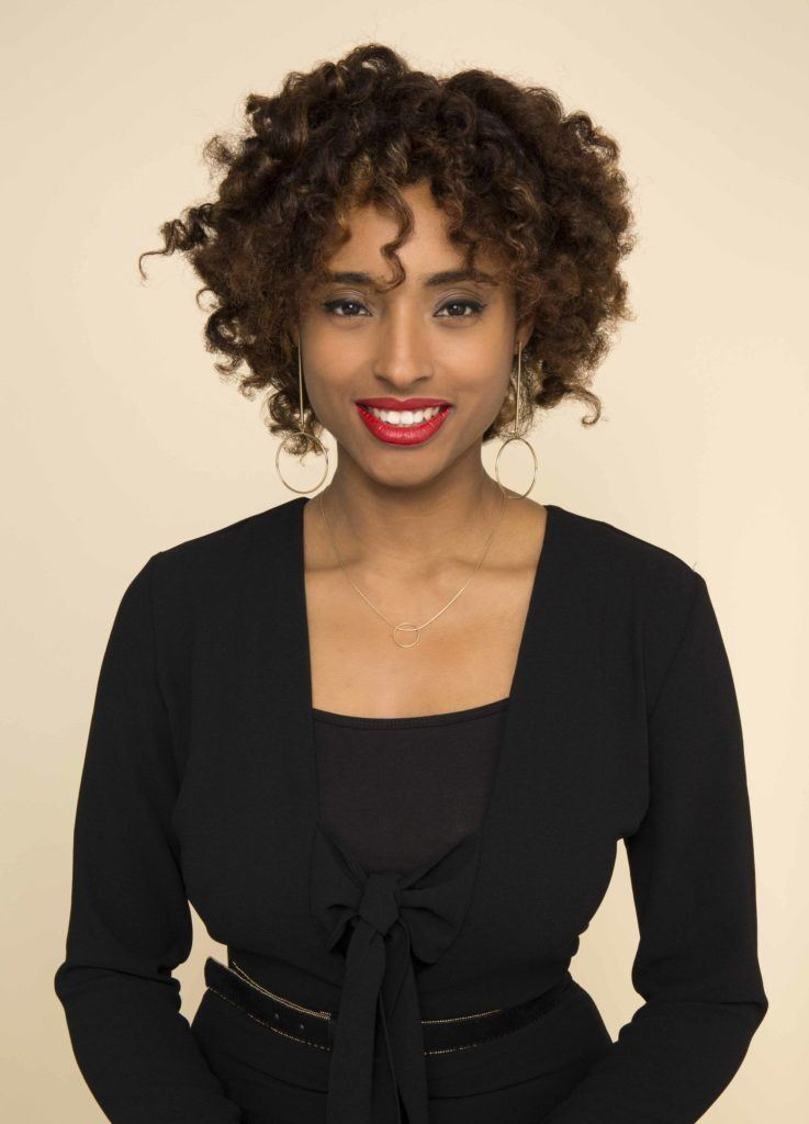 Woman using transitioning hairstyles to grow out chemically straightened hair. Bantu curls.